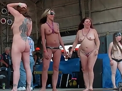 Topless girls get wet at a biker show